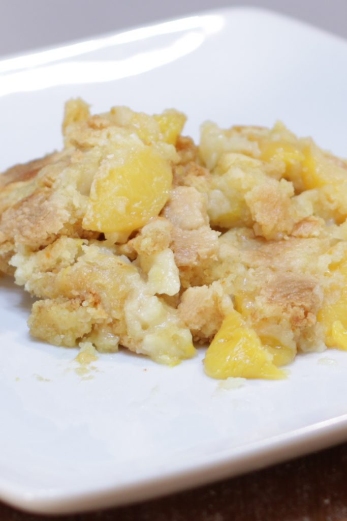 Cake mix peach cobbler on a white plate.