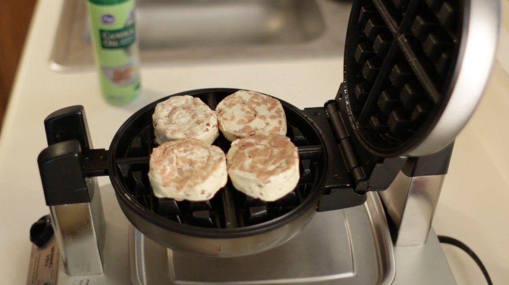 Four cinnamon rolls on a waffle iron.