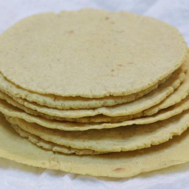Stack of homemade corn tortillas on a plate with paper towel