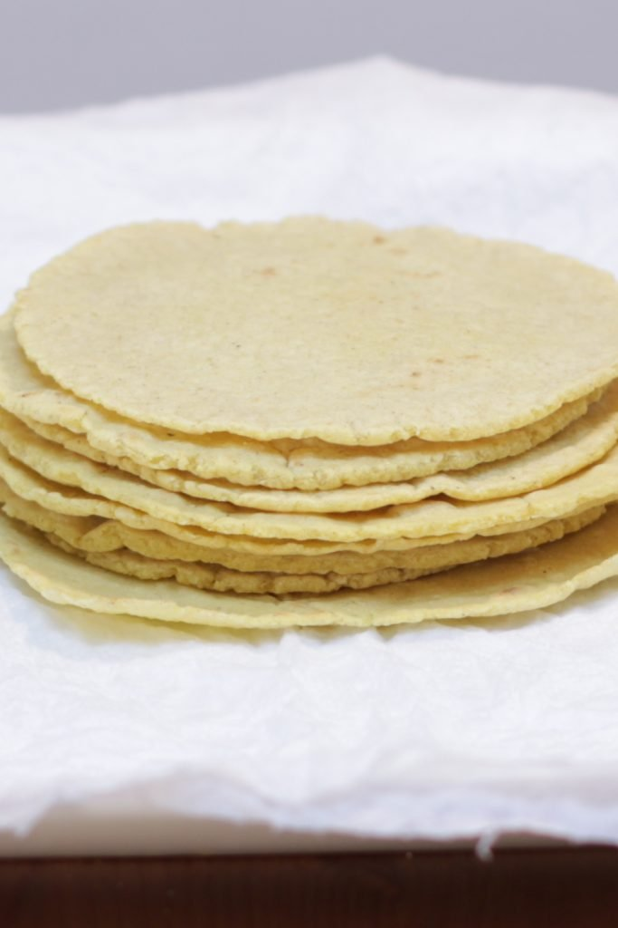 Stack of several corn tortillas on a white paper towel and white plate.