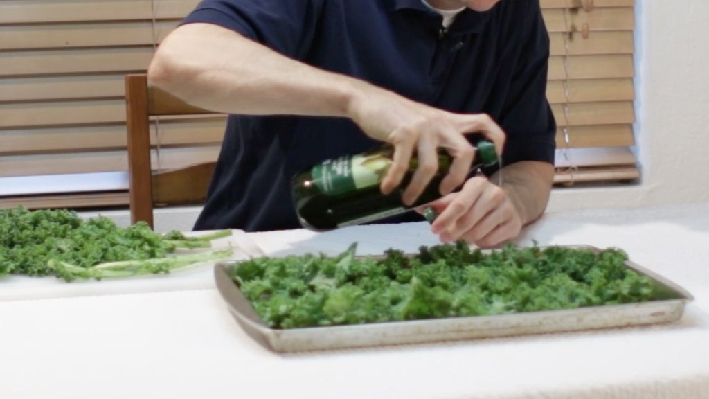 Hand drizzling olive oil over the kale.