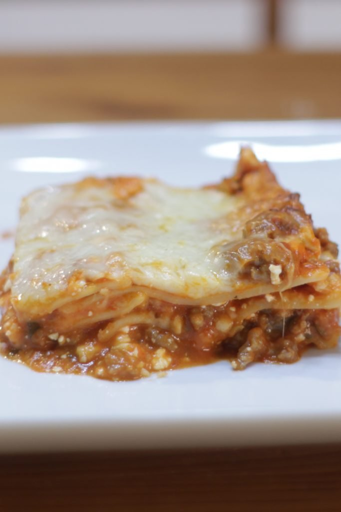 Slice of homemade lasagna on a white plate.