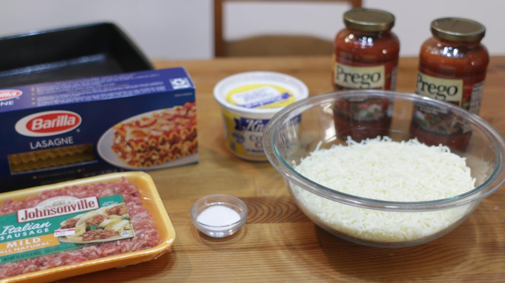 a handful of ingredients on a wooden table including cheese, sausage, sauce, and lasagna pasta