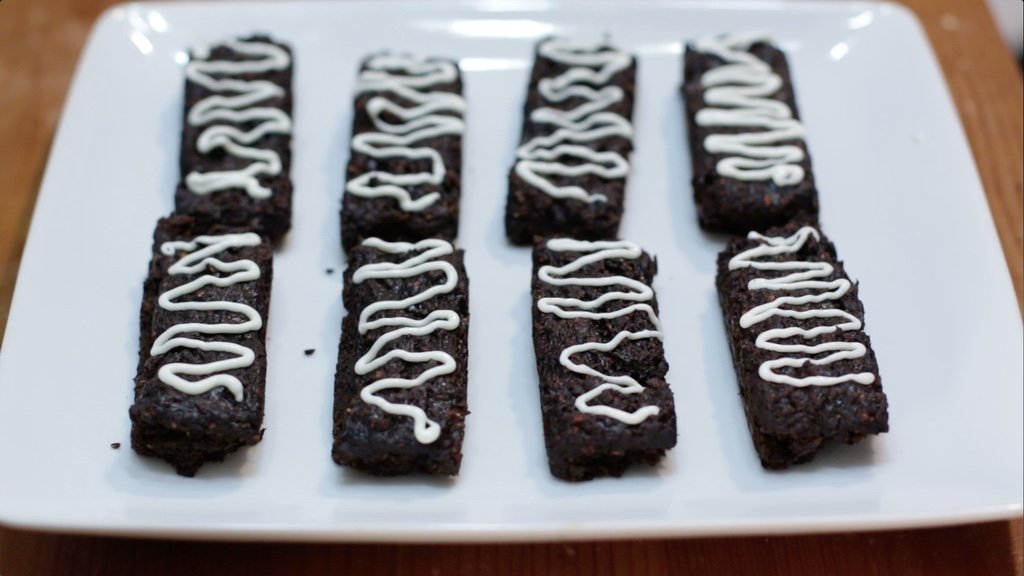 Eight chocolate granola bars drizzled with white chocolate on top of a white plate.