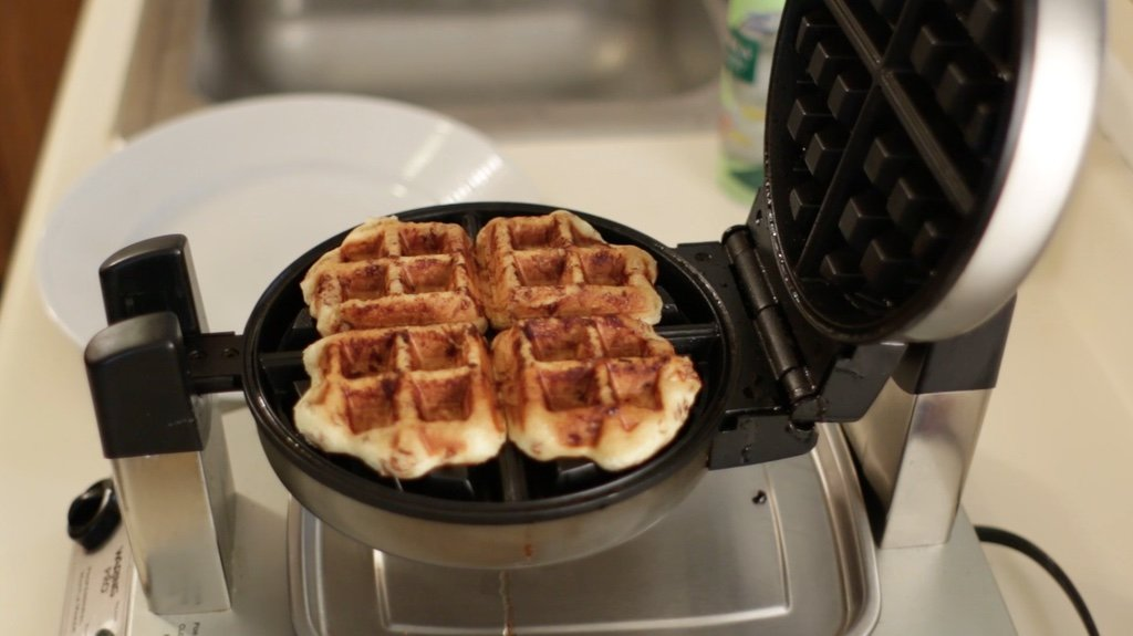 Cooked cinnamon roll waffles on a waffle iron.