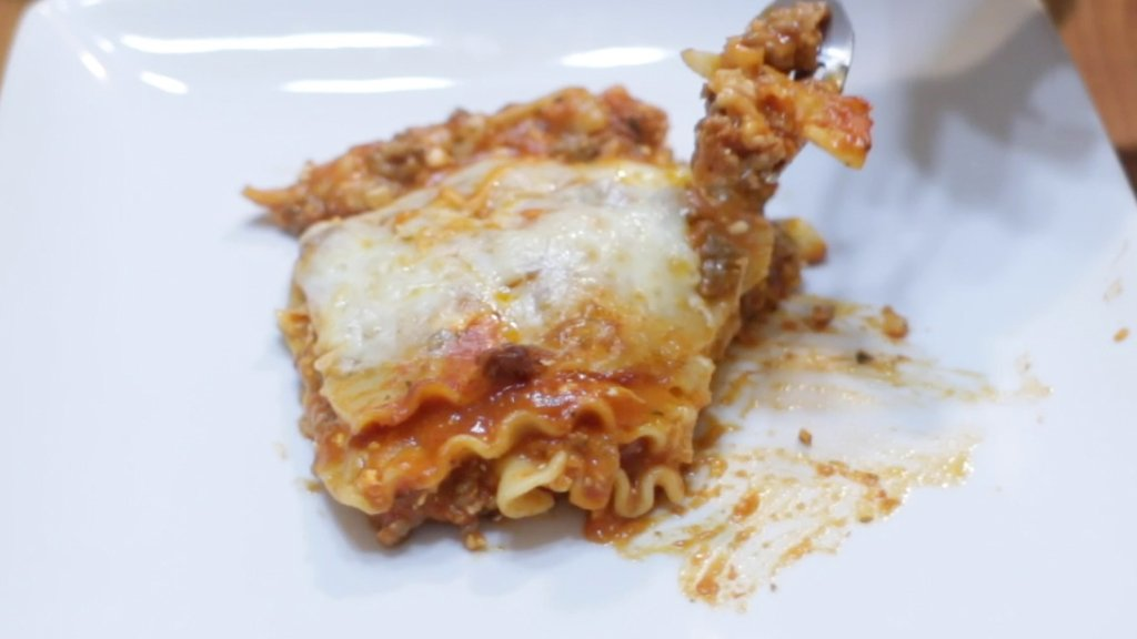 Fork with a bite of lasagna on it.