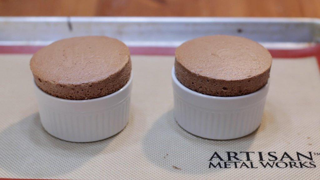 Freshly baked chocolate souffle in white ramekins.