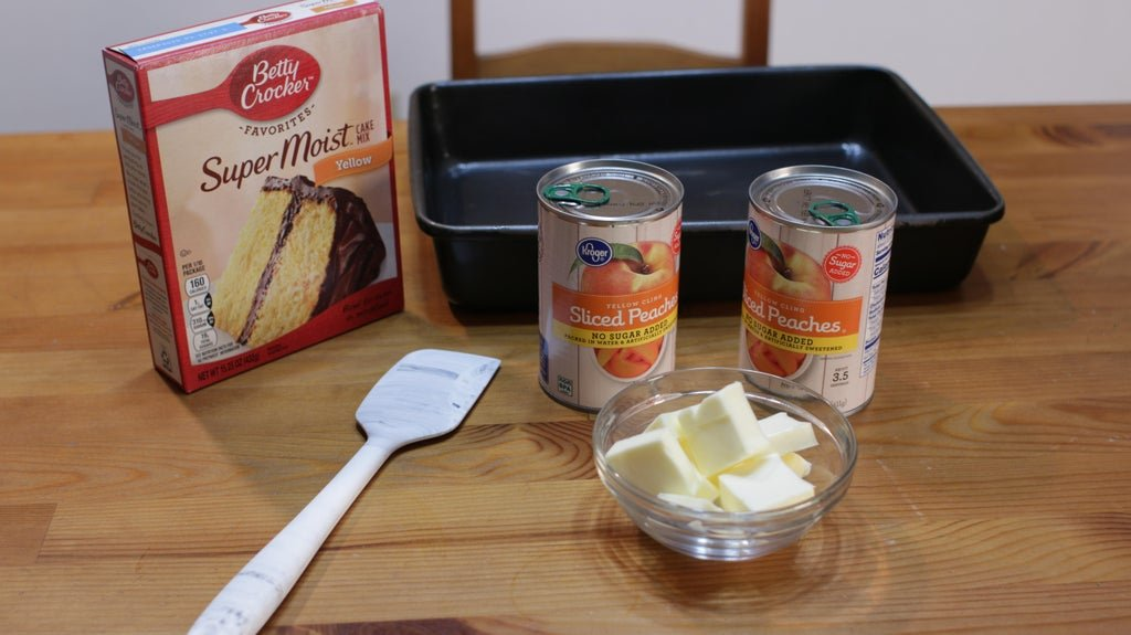 Yellow cake mix in a box, canned peaches, and butter on a wooden table.
