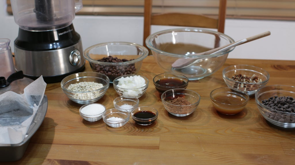 Several ingredients in glass bowls on top of a wooden table.