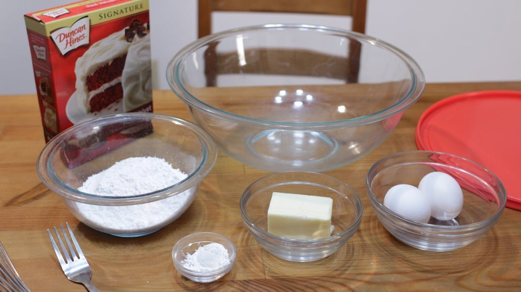 Red velvet cake mix box, powdered sugar, butter, eggs and cornstarch on a wooden table.