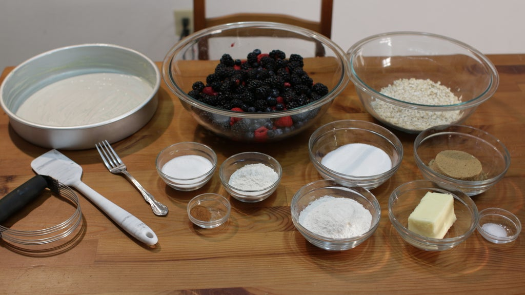 Berries, sugar, oats, butter, etc. in glass bowls on a wooden table.