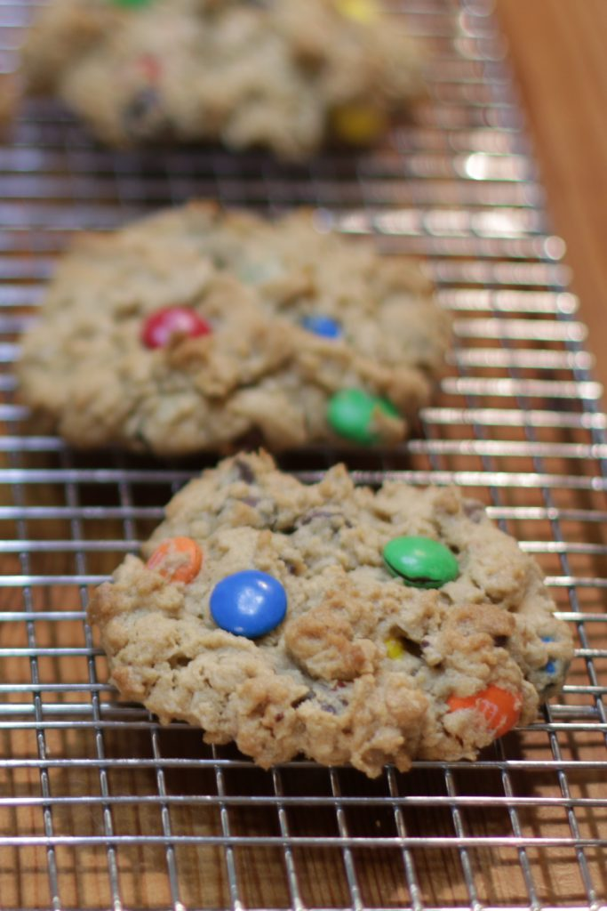 Three monster cookies on a wire rack.