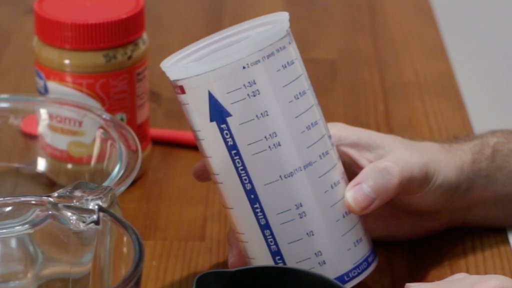Pampered Chef measure all measuring cup on a wooden table.