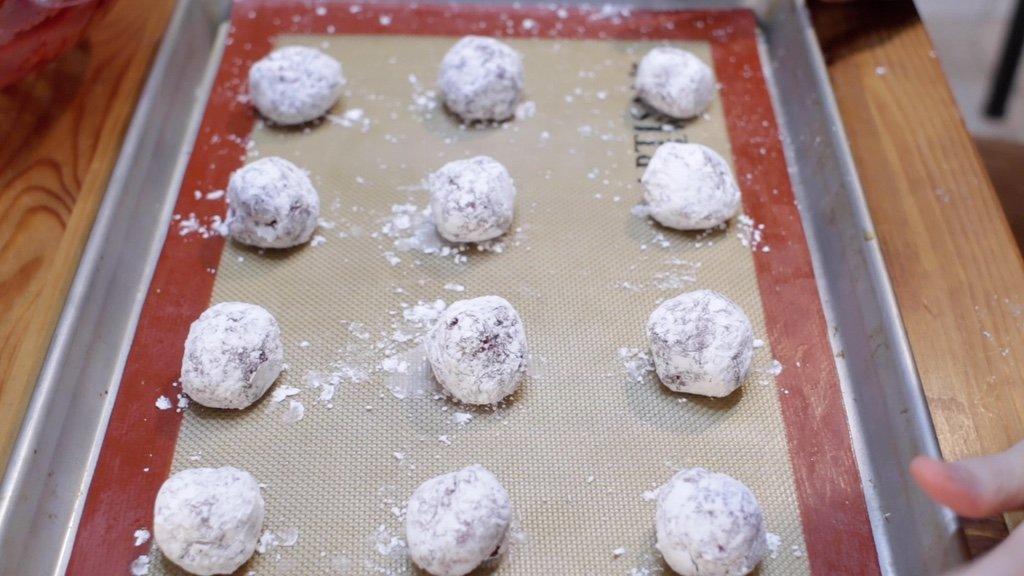 Sheet pan full of unbaked rolled red velvet cake mix crinkles.