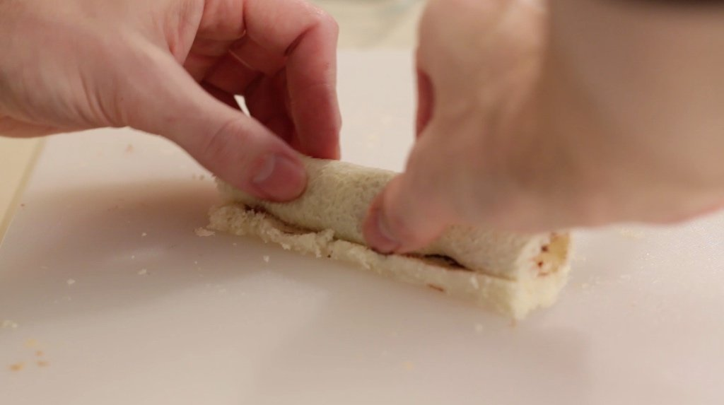 Hand rolling up a French toast roll up