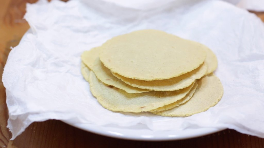 Small stack of 4-inch corn tortillas on a plate with paper towel.