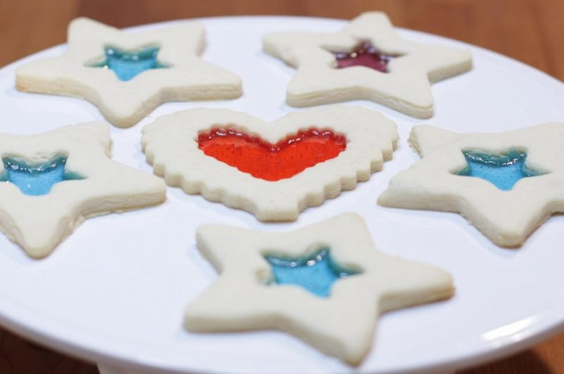 Several stained glass cookies on a white plate.