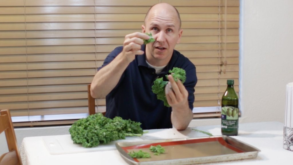 Man holding small pieces of kale above a table.