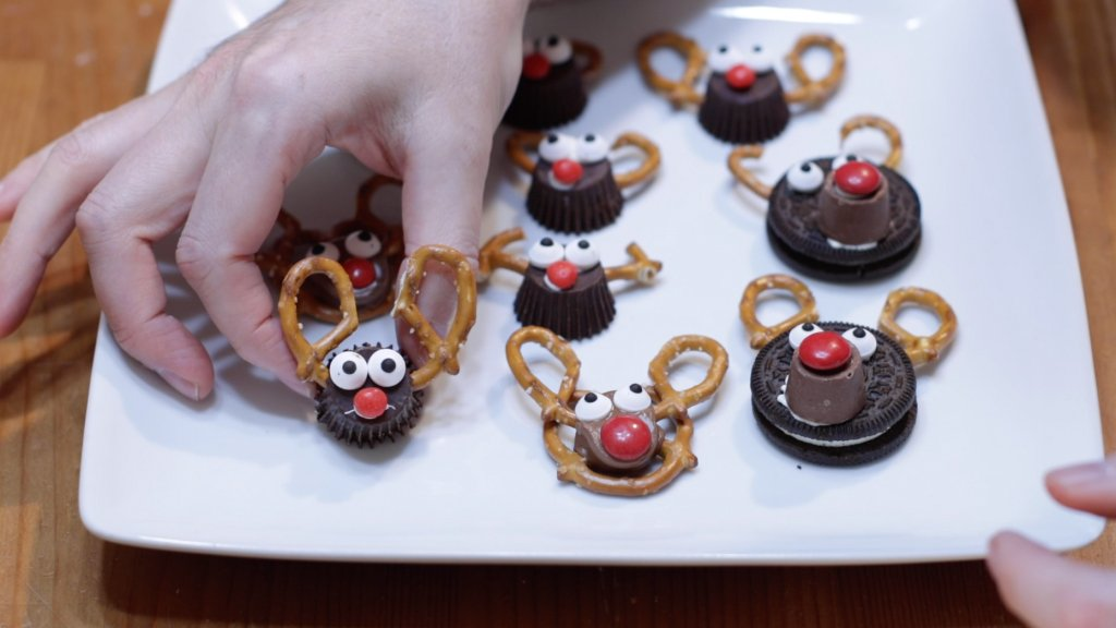 Several variety of pretzel reindeer on a white plate.