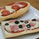 Two French Bread pizzas on a white plate.