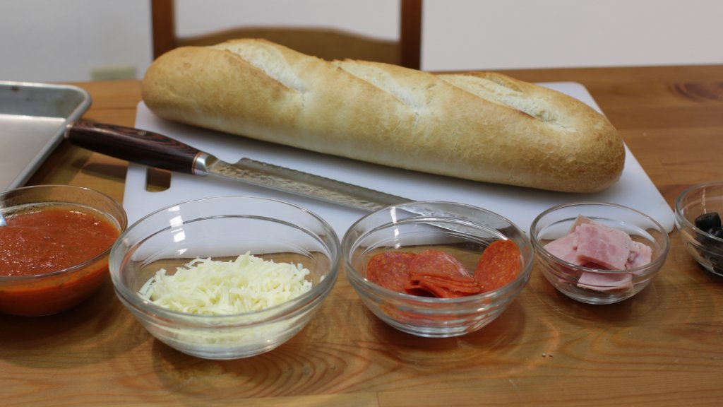 French bread on a white cutting board next to other ingredients in glass bowls.