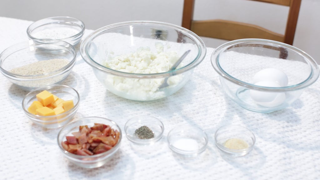 Several ingredients in glass bowls on top of a white table.