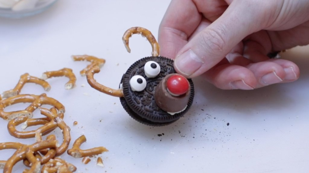 Hand holding a Oreo pretzel reindeer with rolo on it.