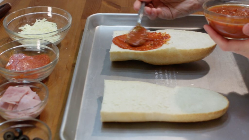 Two slices of French bread on a sheet pan, with pizza sauce being spread on them.