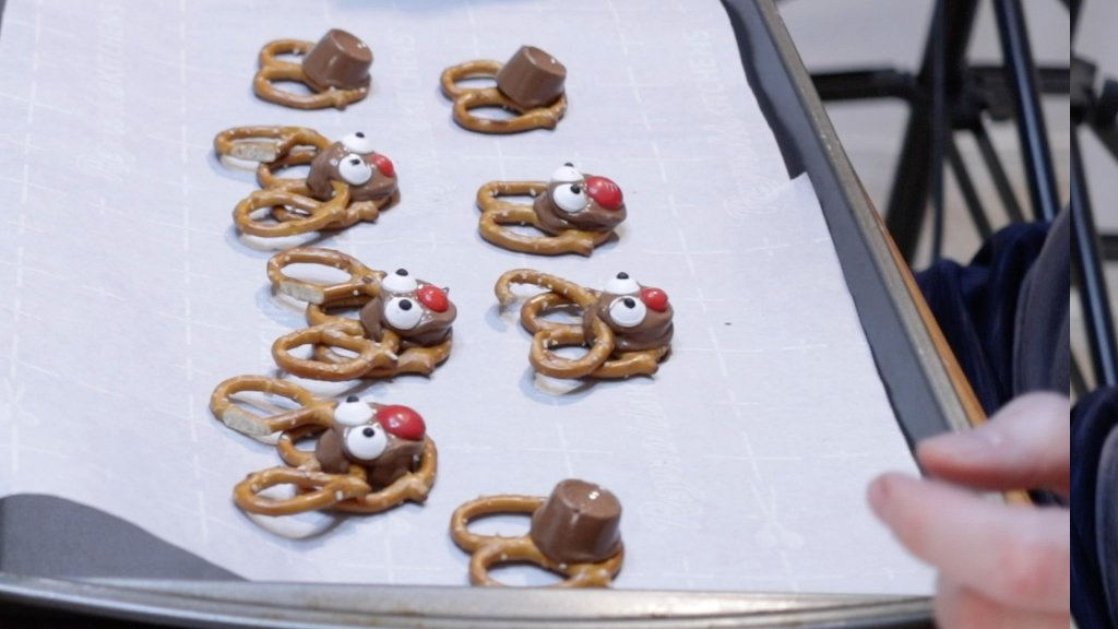 Rolo pretzel reindeer on a sheet pan lined with a silicone baking mat.