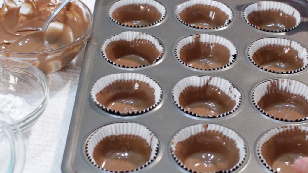 Melted chocolate in paper muffin cups in a muffin pan.