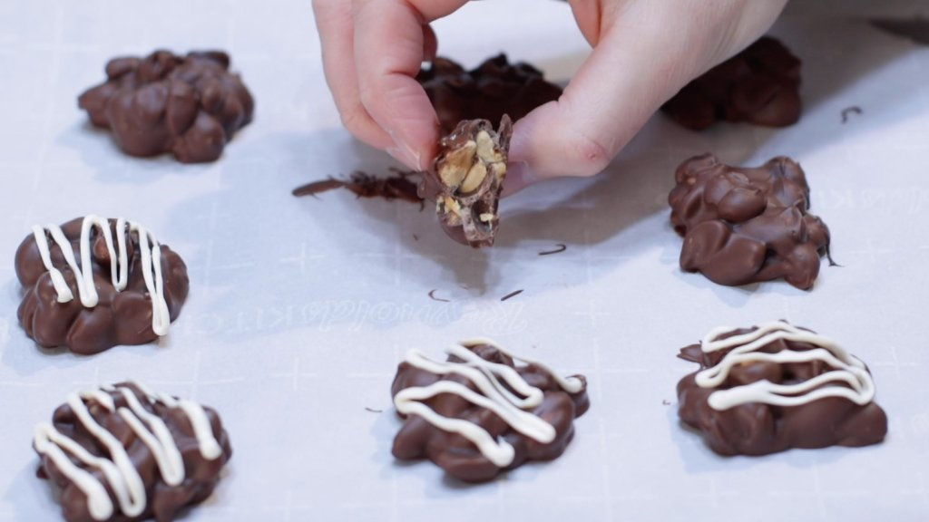 Hand holding a chocolate peanut cluster with a bite out of it.