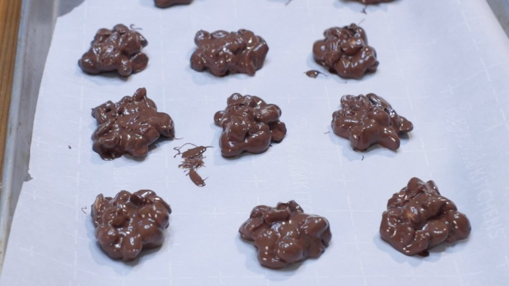 Sheet pan line with parchment paper with chocolate peanut clusters on it.