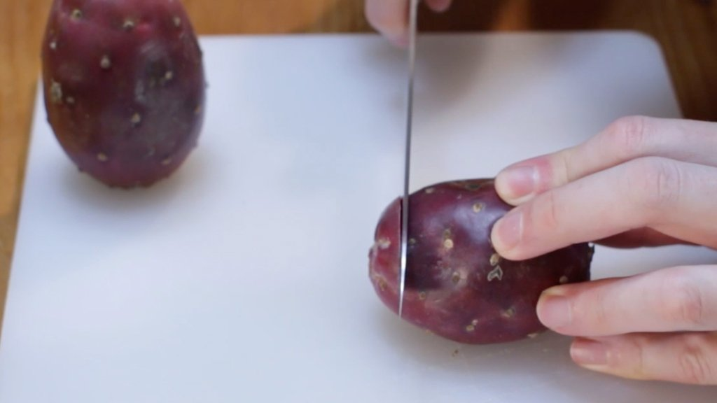 Hand cutting a purple prickly pear cactus fruit.