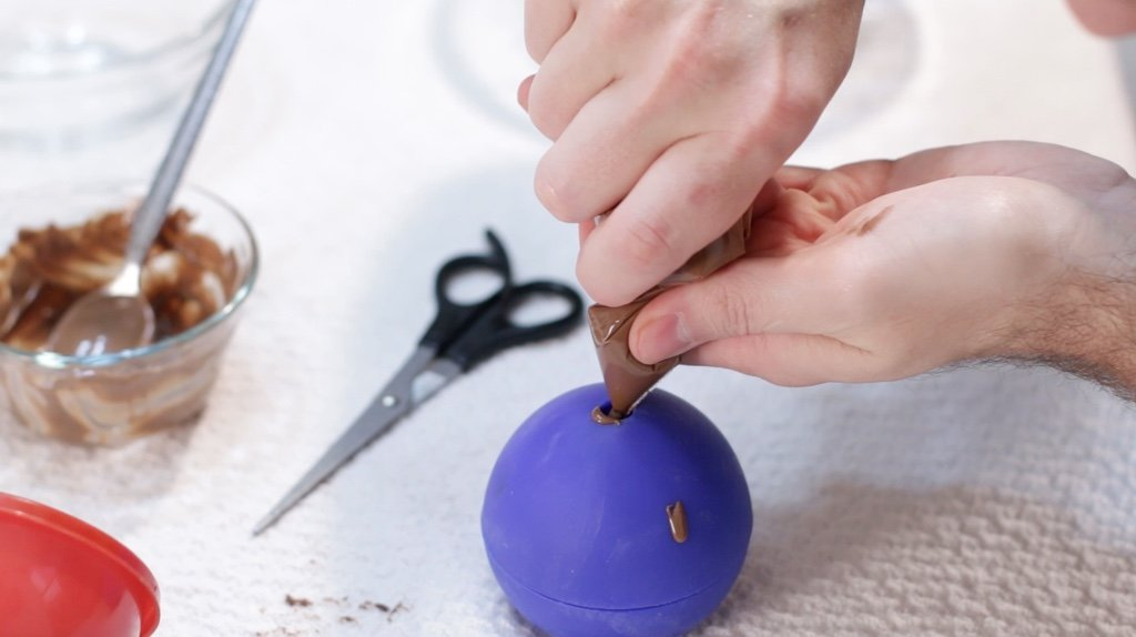 Hand piping chocolate into the hole of a star wars death star mold.