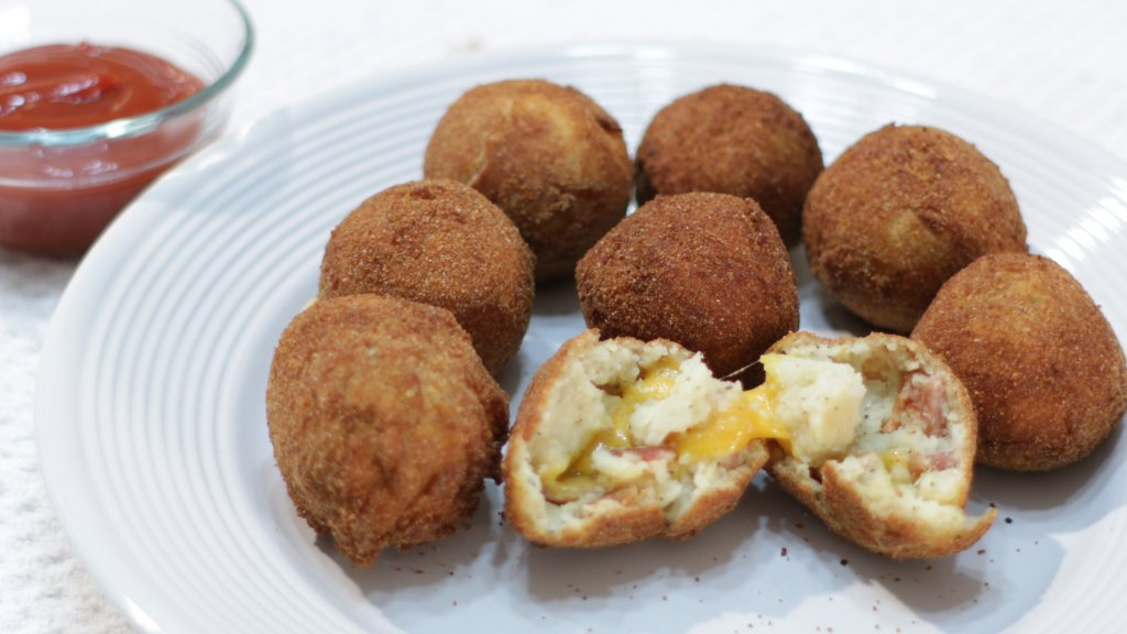 Finished bacon and cheese mashed potato balls on a white plate.