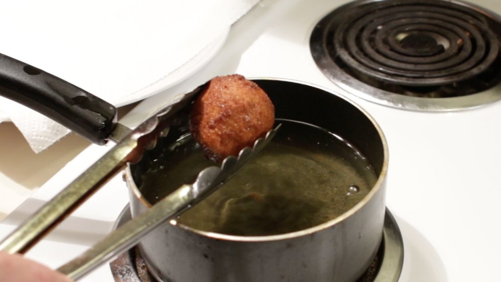 Tongs holding a fried bacon and cheese mashed potato ball over a small pot of oil.