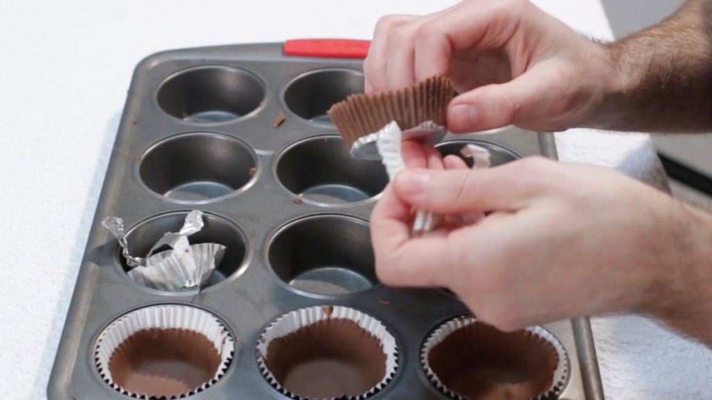 Hands unwrapping chocolate cups from paper cups, for the strawberry cheesecake mousse.