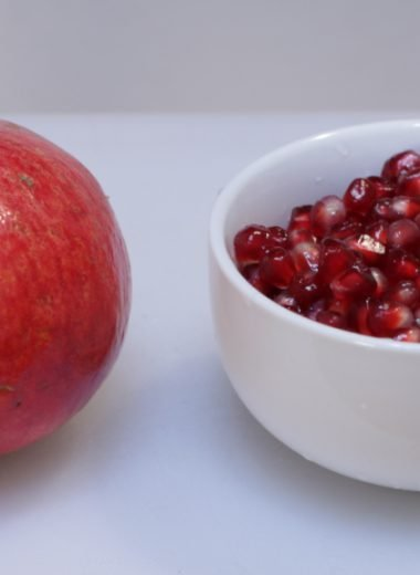 a pomegranate on a white cutting board next to a bowl of pomegranate seeds