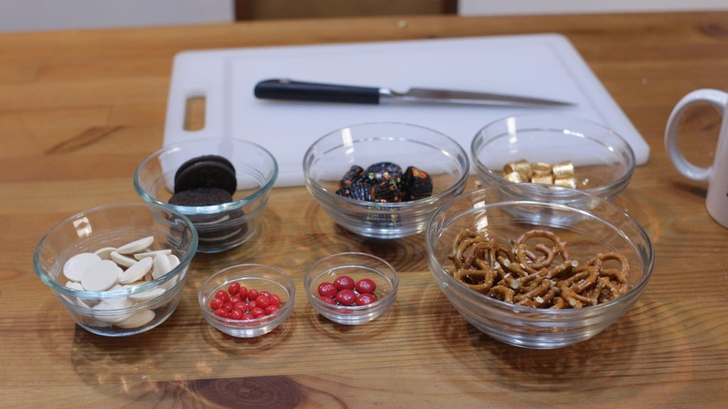 Pretzels, Rolos, and other ingredients in glass bowls on a table.