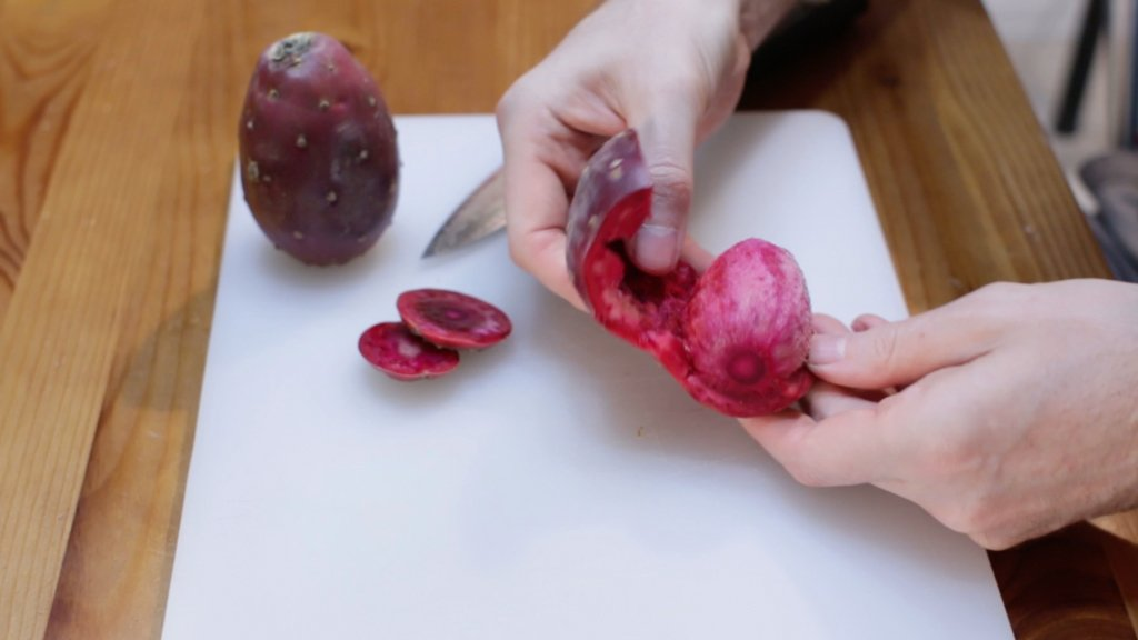 Hand peeling a prickly pear fruit.