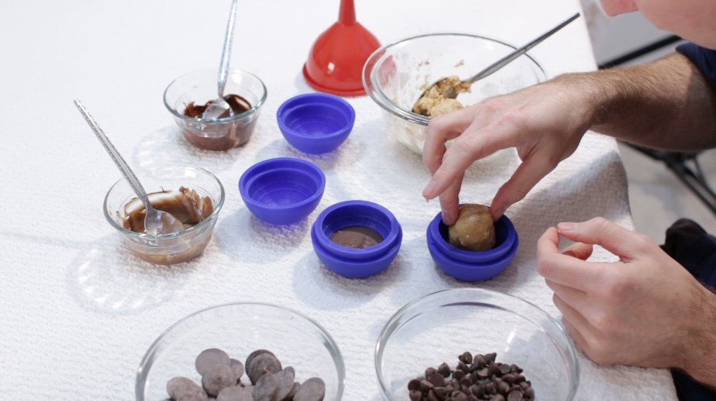 Hand placing a ball of peanut butter cup filling in a Star Wars death star mold.
