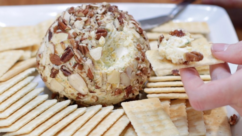 Homemade easy cheese ball on a plate with crackers.