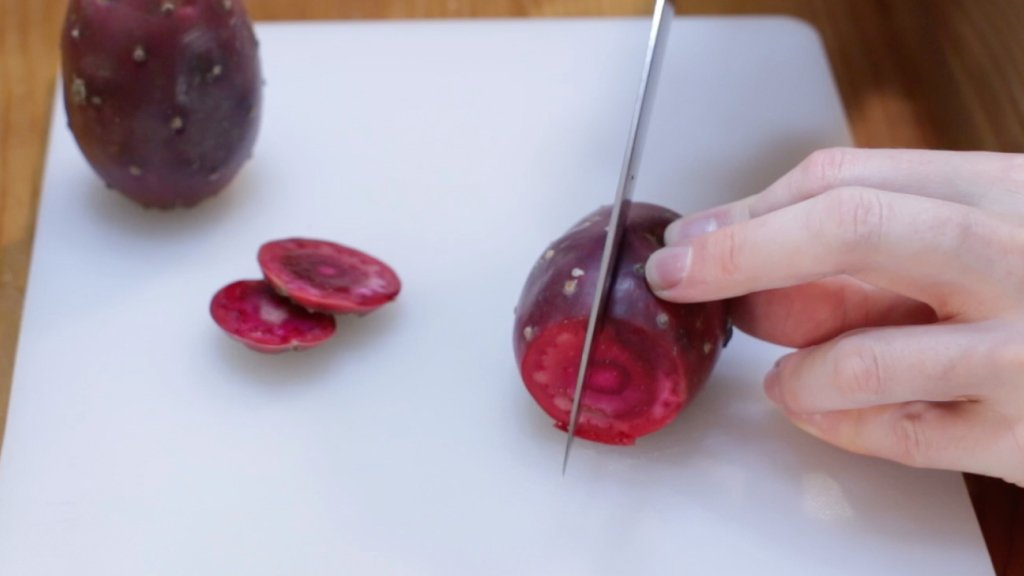 Knife slicing a prickly pear lengthwise.