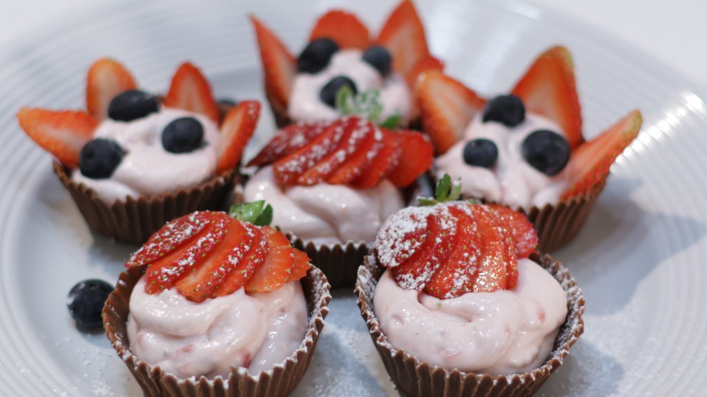Six strawberry cheesecake mousse chocolate cups on a white plate.