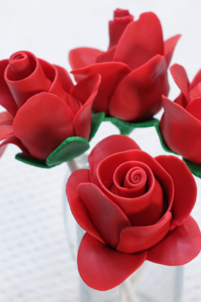 Chocolate strawberry fondant roses on a white table.