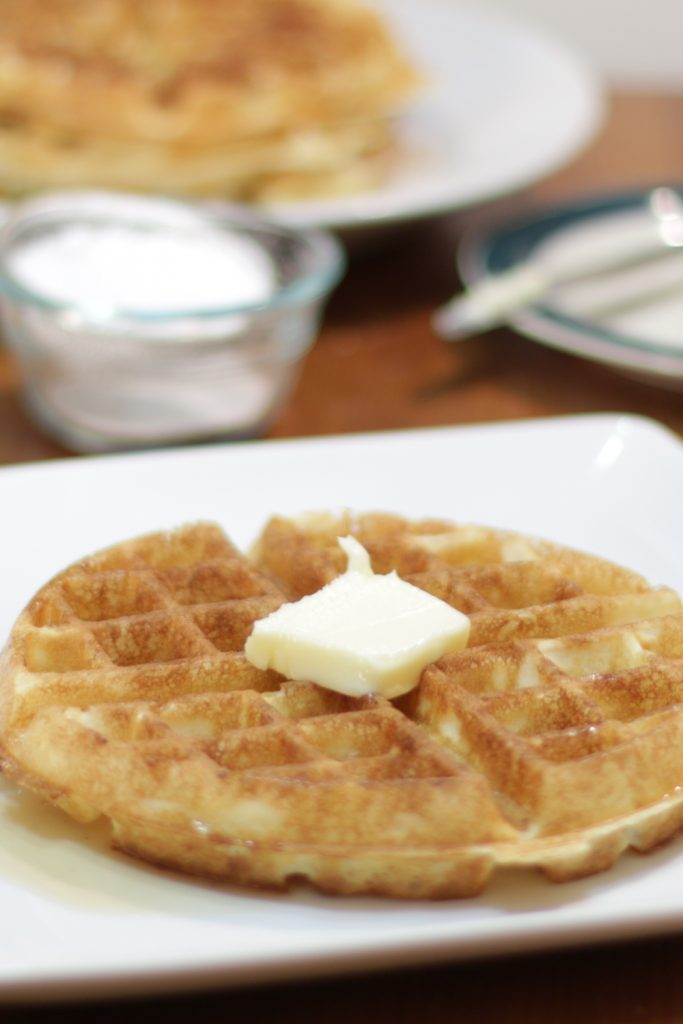 Homemade waffles on a white plate on a table.