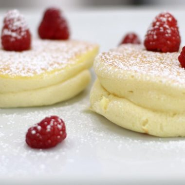 Japanese souffle pancakes on a white plate with raspberries