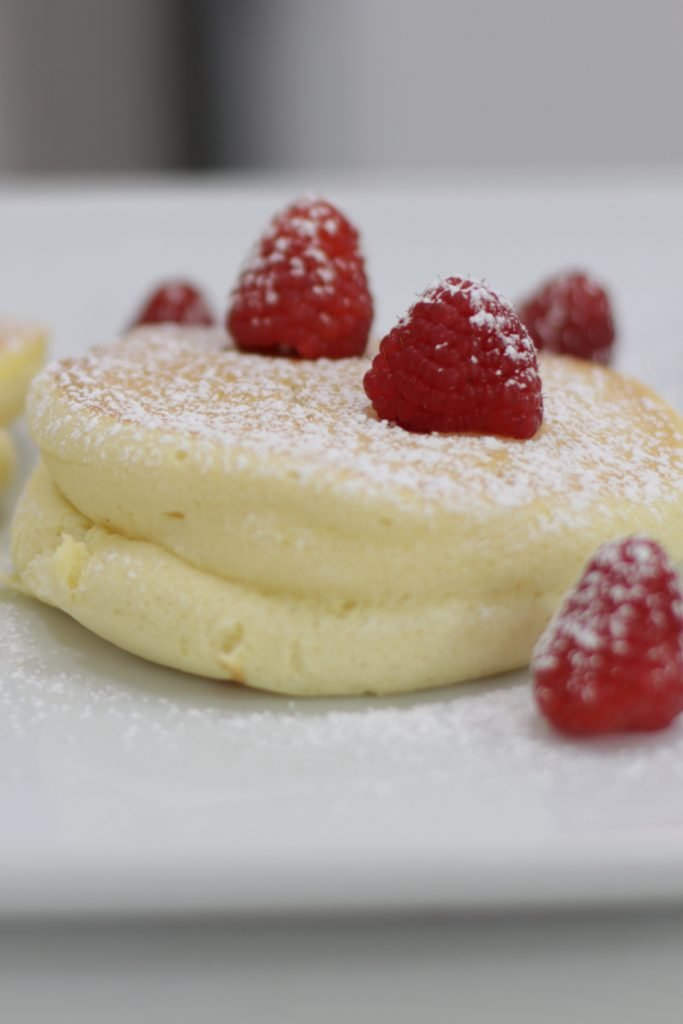 Japanese souffle pancake on a white plate with raspberries and powdered sugar.