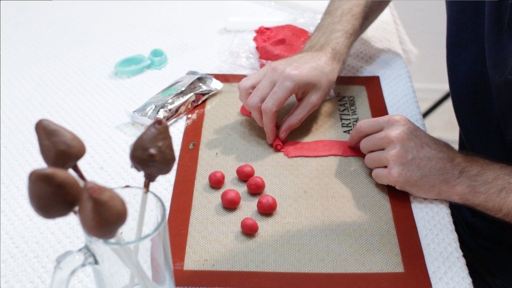 Hand rolling up a small piece of the red fondant for the chocolate rose