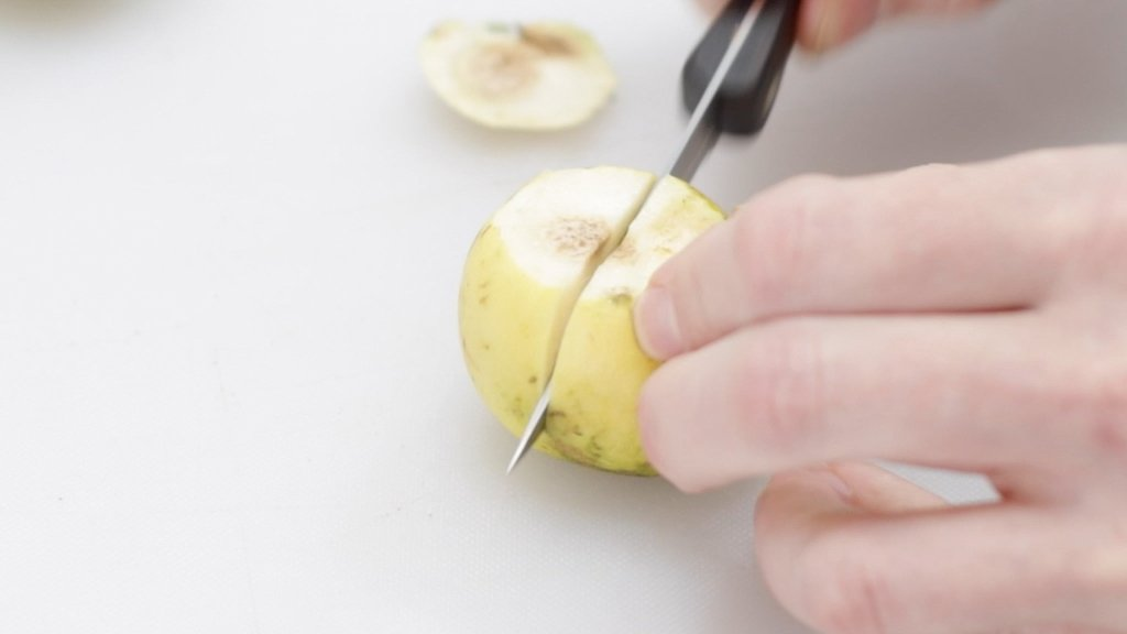 Hand with knife cutting a Mexican guava.